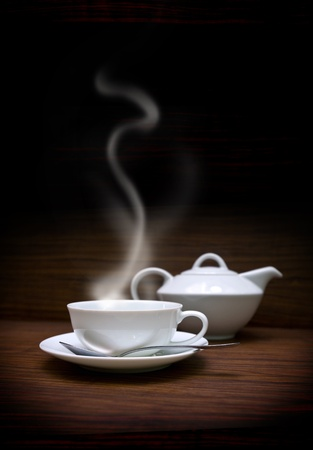 nonalcoholic: white cup and teapot on the oak surface