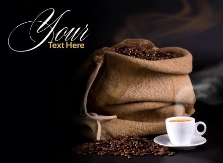 granos de cafe: bolsa de granos de café y café caliente sobre un fondo oscuro Foto de archivo