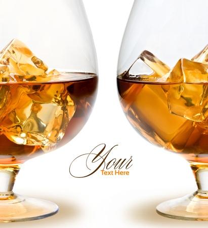 scotch: Glas whisky met ijs op witte achtergrond