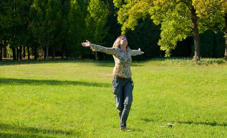 s.Carefree adorable girl with arms out in field. photo
