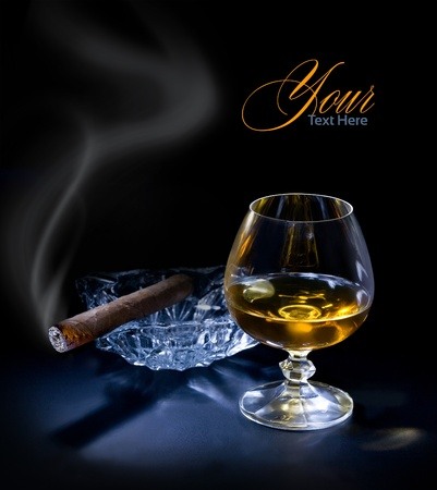 Glass of cognac with a cigar on dark sackground photo