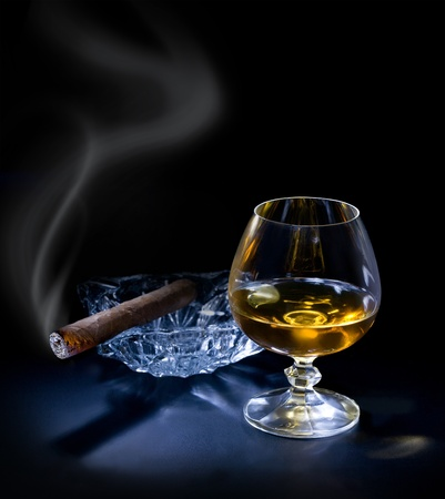 drunks: Glass of cognac with a cigar on dark sackground Stock Photo