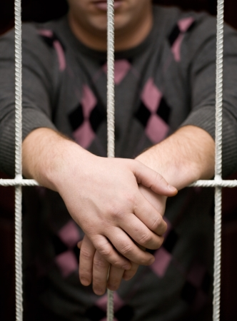mans hands behind bars in jail or prison photo