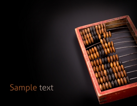 old wooden abacus on a dark background with place for text photo