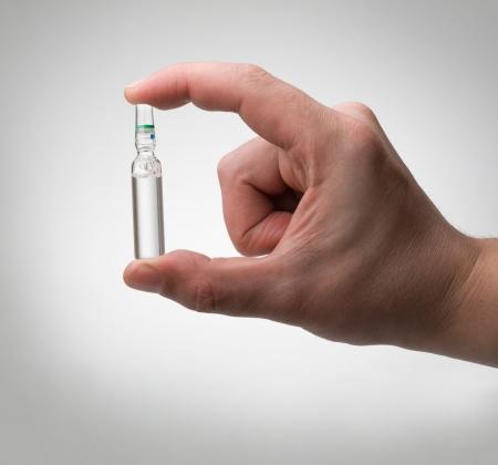 vacunación: ampolla en una mano en un fondo gris claro