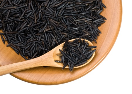 black rice: wooden plate with grains of black  rice on a white background with clipping paths