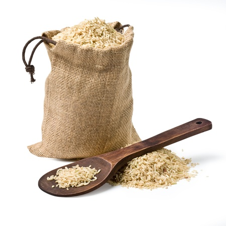 brown rice: bag of rice and a wooden spoon on a white background  keeping paths Stock Photo
