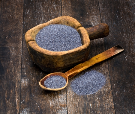 doughy: poppy seeds in a wooden bowl on a background of the old wooden table