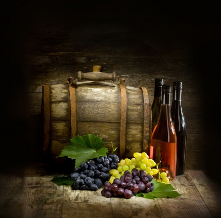 Still life with red and white wine, bottles, grapes and barrel
