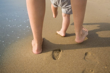 little girl barefoot: Mother and child walking on a sandy beach