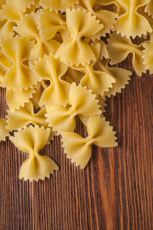 bow tie pasta on wooden background close up photo
