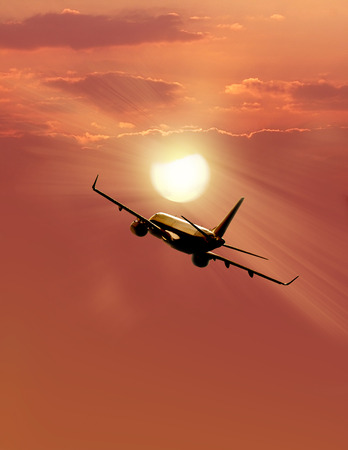 Airplane taking off at sunset. Silhouette of a big passenger or cargo aircraft, photo