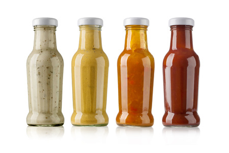 especias: salsas de barbacoa en botellas de vidrio en el fondo blanco Foto de archivo