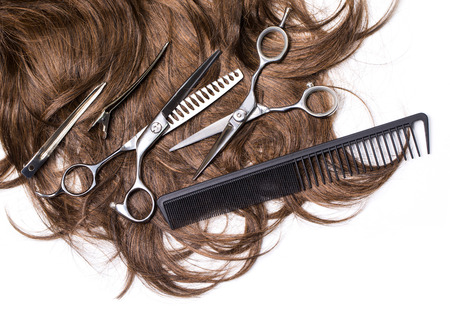 Long brown hair with scissors on close up isolated on white background Stockfoto