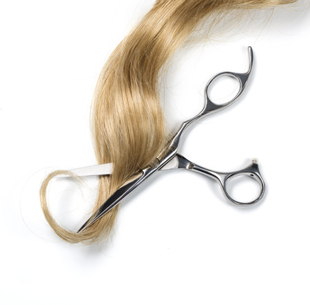 Long blond hair and scissors isolated on white background Foto de archivo