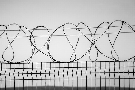 Barbed wire on dark fence. Monochrome silhouette photo photo