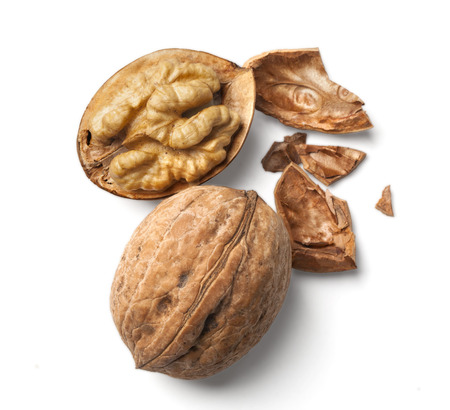 walnut and a cracked walnut isolated on the white background with clipping past