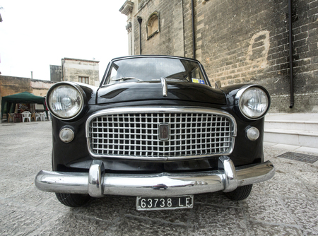 fiat: PUGLIA, ITALY-  MAY 02.2015.  Exhibition of old cars. Old black Fiat on a city street