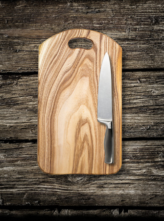 paring: Empty chopping board with a sharp paring knife on a distressed grunge wooden table in a rustic kitchen,