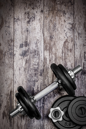 dumbells: Dumbbells on the wood background and vignetting.