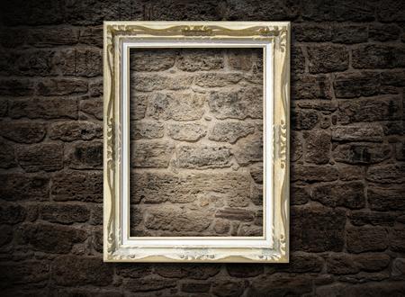light spot: old frame on a brick wall dark baground Stock Photo