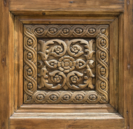 porte bois: fragment of a carved wooden door in the Basilica, Italy