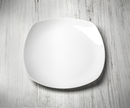 lunch table: white plate on wooden background close up