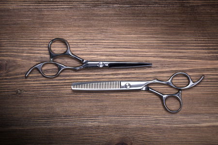 hairdressing equipment like different scissors on brown wooden table in professional hairdressing salon