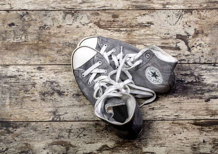 converse: CHISINAU, MOLDOVA - DECEMBER 24, 2015: Gray Converse shoes on wooden planks
