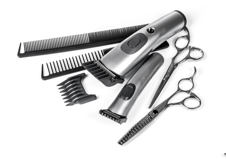 haircutting: hair clipper, comb and scissors on white background