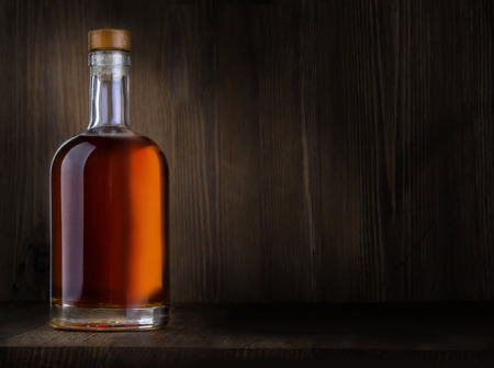 Bottle of whiskey on a wooden background with copy space