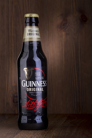 guinness beer: CHISINAU, MPLDOVA - Ferbruary 05, 2016: A bottle of Guinness beer on a wooden background. Guinness is one of the most successful beer brands worldwide.