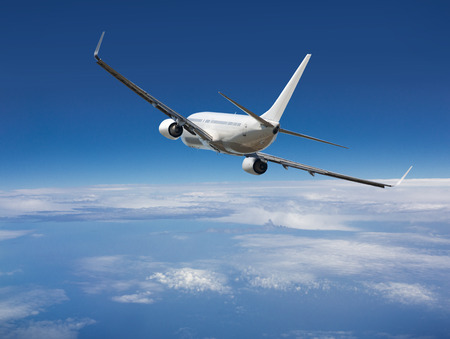 White passenger wide-body plane. Aircraft is flying in blue cloudy sky over the sea.
