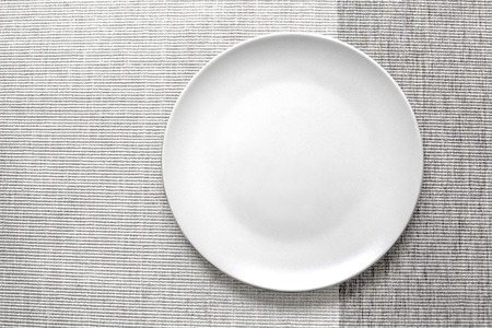 Empty white plate on grey napkin, top view, with clipping path Stock Photo