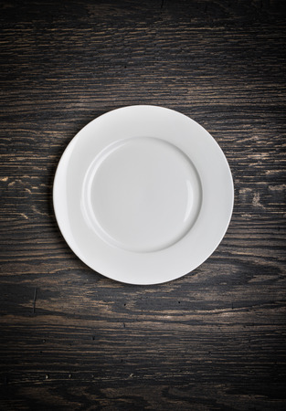 blank spaces: Empty white plate on wooden table background