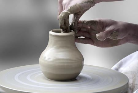 여자의 손을 도자기의 바퀴에 세라믹 컵 만들기
