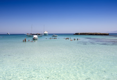 tour boats: Blur background Tour boats moor in the clear turquoise water of popular tourist attraction Blue Lagoon on a sunny day Stock Photo