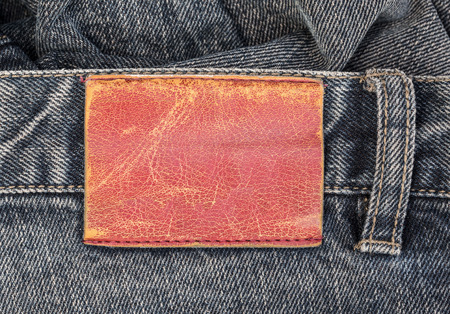 leather label: blank  leather label on blue jeans background