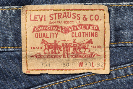 levi: Chisinau, Moldova - August 19, 2016: Closeup of Levis leather jeans label sewed on a blue jeans isolated on white background.Levi Strauss & Co is a privately held American clothing company.