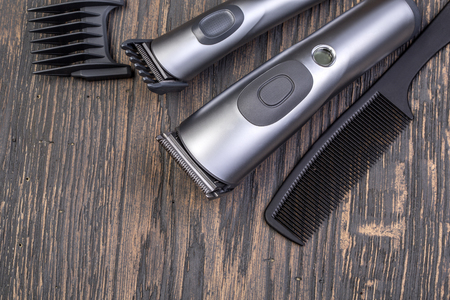 hairclipper: Setting with hair clipper and comb on wooden background