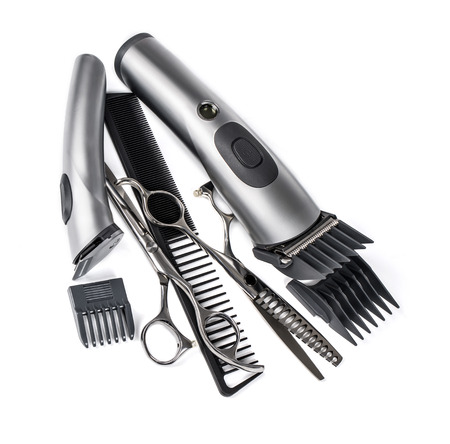 Hairdressing industry. Professional hairdressing tools. Comb, scissor, clippers and hair trimmer isolated on white background Stock Photo