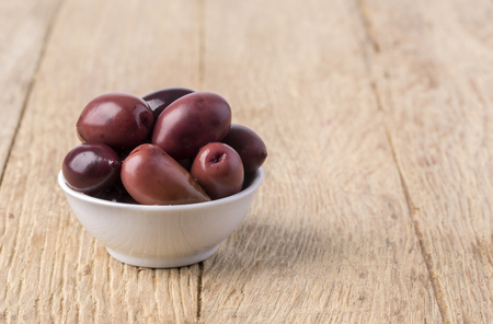 kalamata: olives into in a bowl on wooden table background Stock Photo