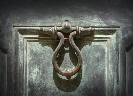 antique background: antique door-knocker on old door background