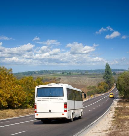 cornering: White tourists bus cornering on street road background Stock Photo
