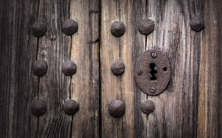 wood panelled: Keyhole in an old paneled wooden door; rusty and weathered. This image has been processed to make a more impactful, dramatic shot. Stock Photo