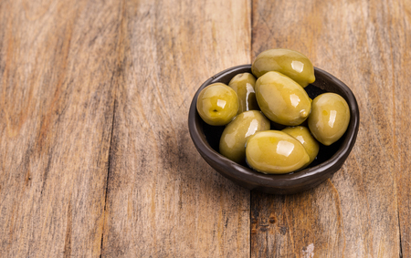 giant green olives in olive bowl on wood background, shallow focus Stock Photo