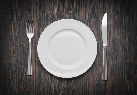 blank spaces: Photo of an empty white plate with knife and fork on a rustic wooden table.