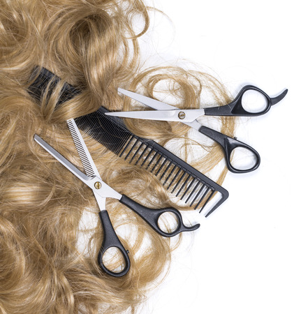 Hairdressing scissors with blonde hair. Isolated background