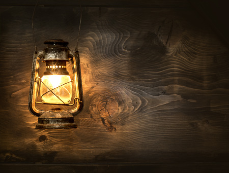 kerosene lamp: The old kerosene lantern hanging on the wooden wall Stock Photo