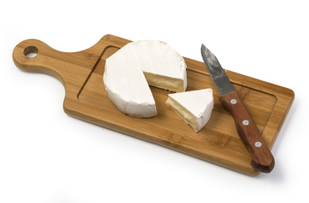 Camembert cheese with knife on wooden board with clipping path